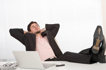 Young businessman in black suit relaxing at office