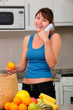 woman on phone laughing while unpacking groceries