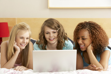 Group Of Three Teenage Girls Using Laptop In Bedroom