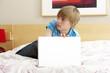 Guilty Teenage Boy Using Laptop In Bedroom