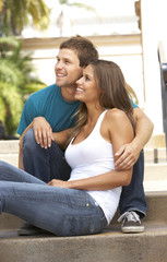 Young Couple Sitting On Steps Of Building