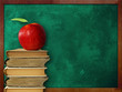apple on stack of books  against  classroom chalk board
