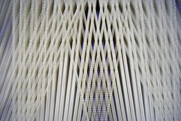 fili di stoffa intrecciati nelle maglie di un telaio
