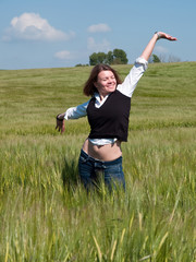 Beautiful attractive young happy woman in a wheat field