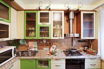 Green Kitchen interior with many utensils