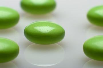Grüne Medizindragees auf weißem Grund
