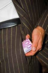 Man zieht Geldrolle aus der Tasche