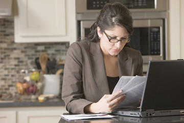 Hispanic businesswoman with paperwork and laptop