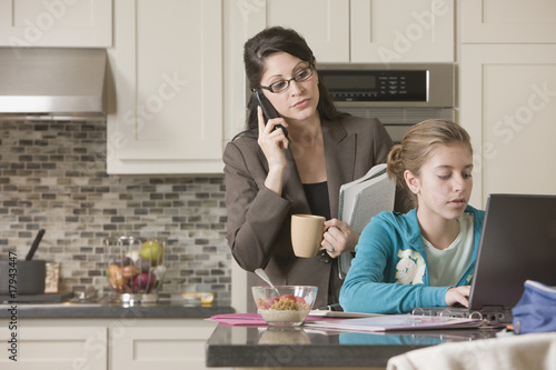 Hispanic mother watching daughter using laptop