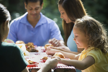 Hispanic family saying grace at picnic table
