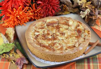 Whole apple kuchen cake in fall setting.