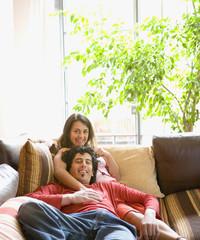 Couple sitting on sofa hugging