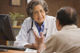 Senior Hispanic female doctor talking to patient in office
