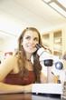 Teenaged girl with microscope in classroom