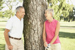 Senior couple leaning against tree on golf course