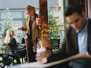 Businesswoman holding to go coffee in cafe