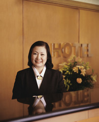 Asian woman behind hotel reception desk