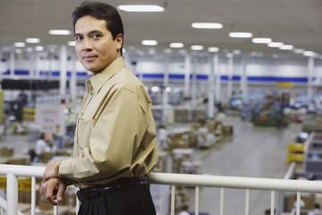 Asian businessman on balcony overlooking warehouse