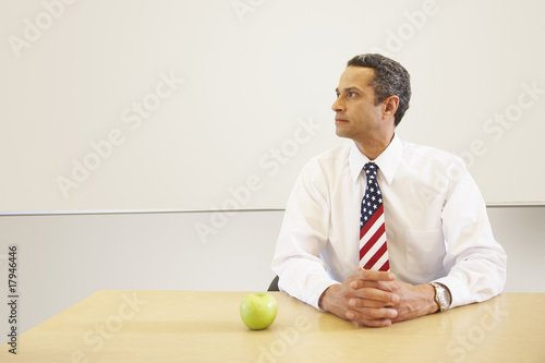 Hispanic male teacher with American flag tie and apple on desk