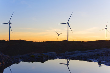windmills at sunset in the top of a montain, whith reflexes in t