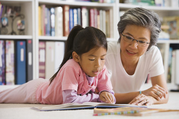 Asian mother and daughter reading in library
