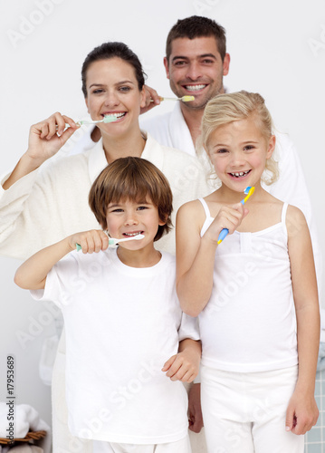 Parents and children cleaning their teeth in bathroom