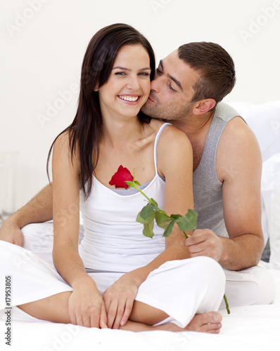 Man kissing a woman and holding a rose
