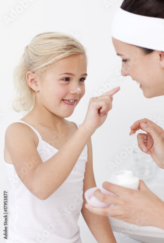 Mother and daughter putting cream on face