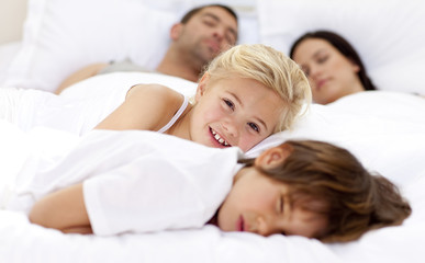 Smiling daughter relaxing with her brother and parents in bed