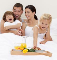 Family having breakfast in bed in the morning