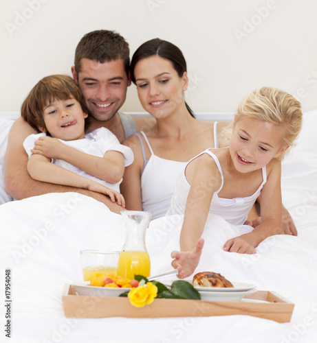 Happy family having breakfast in bedroom