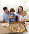 Parents and children eating pizza in living-room