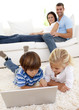 Children using a laptop and couple lying on sofa