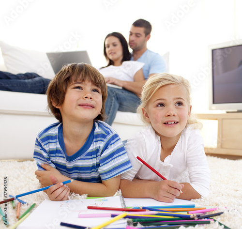 Children painting in living-room and parents on sofa