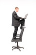 Businessman standing on chair and working on notebook