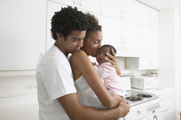 African parents hugging baby in kitchen