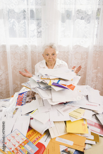 Senior woman looking at pile of bills