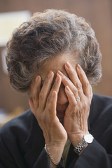 Senior Hispanic woman covering face with hands