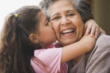 Hispanic granddaughter kissing grandmother's cheek