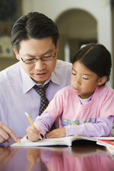 Asian father helping daughter with homework
