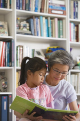 Asian mother reading to daughter in library
