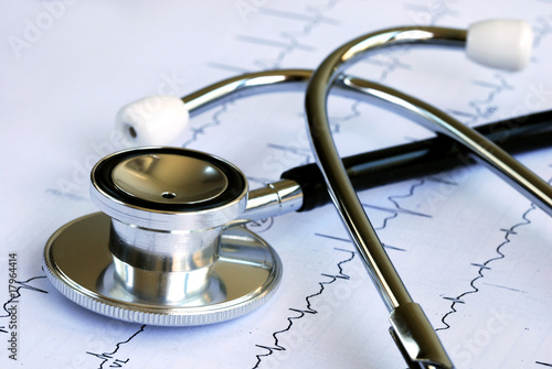 A stethoscope on the top of the EKG chart - 17964414