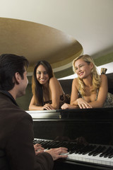Multi-ethnic women watching piano player