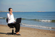Business woman on phone/laptop at the beach