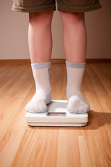 Boy measures weight on floor scales