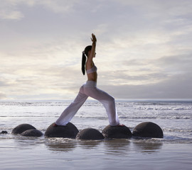 Pacific Islander woman practicing yoga at beach