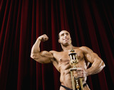 Hispanic male body builder holding trophy