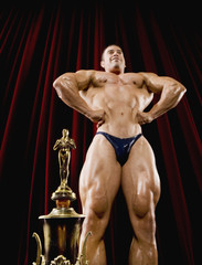 Hispanic male body builder flexing next to trophy