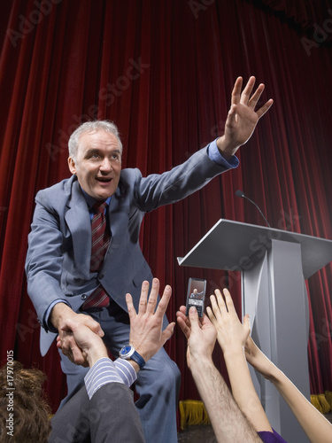 Politician on stage shaking hands with crowd