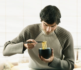 Young man eating noodles